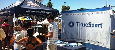 TrueSport and USA swimming outdoor event featuring table and tent