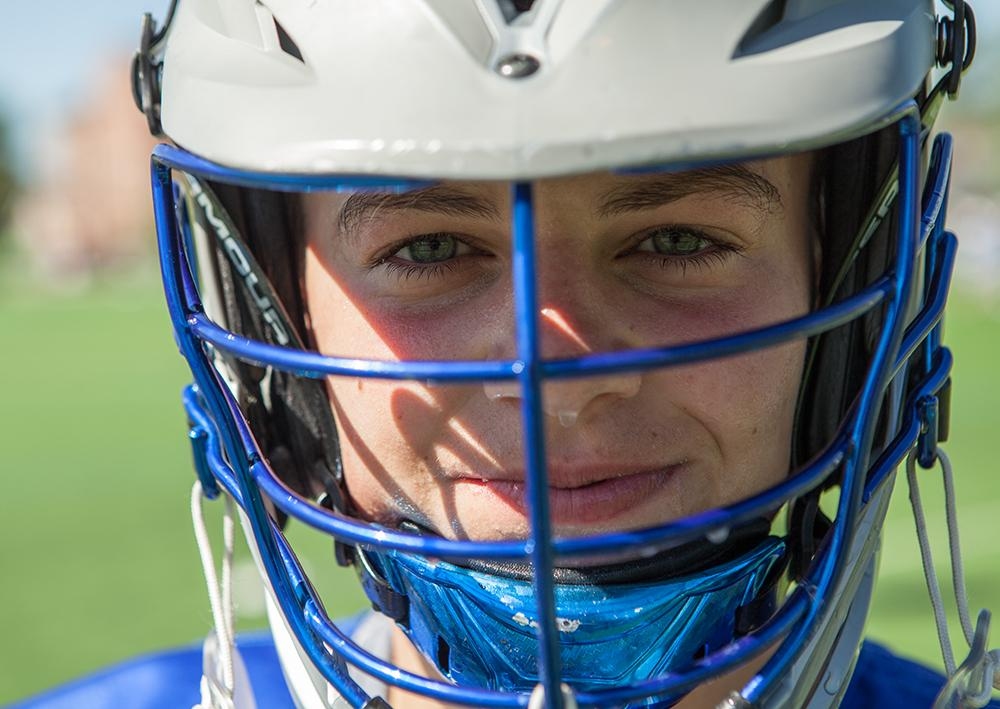 Young male lacrosse player smiling at camera