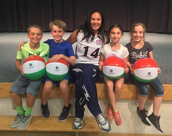 Candace Vering sitting with children holding TrueSport beachballs