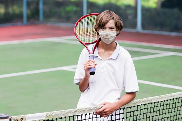 Young white boy holding a tennis racket with a mask over his nose and mouth.