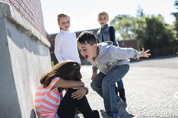 Young white boy yelling at a girl sitting on the ground with her head in her hands.