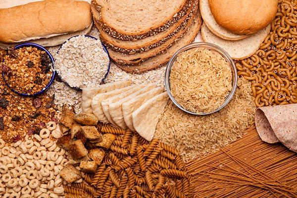 a variety of breads and whole grains including pasta on table