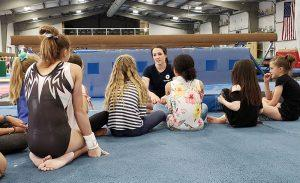 chellsie memmel sitting and talking to young gymnast athletes