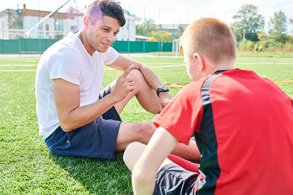 Male coach talking to a young male soccer player while sitting on the field.