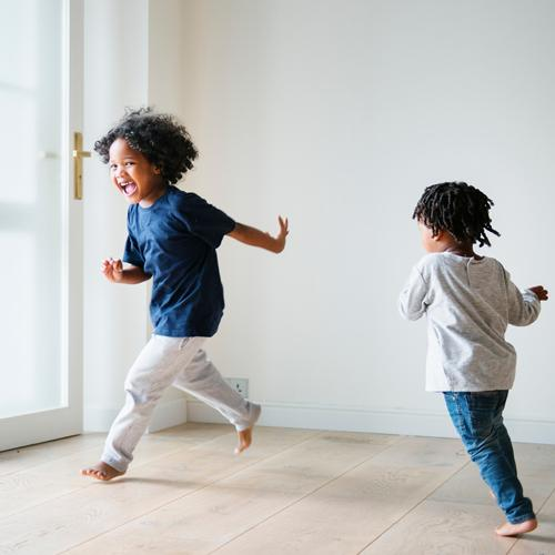Two black children happily running around a house.