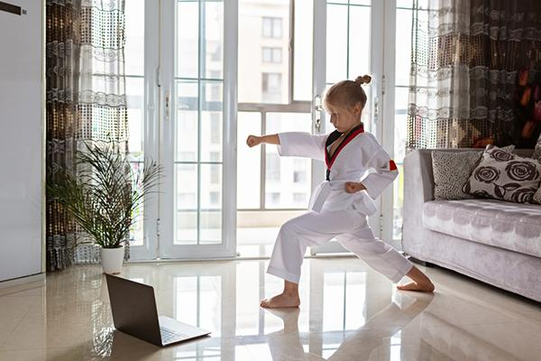 Young white girl doing taekwondo in her living room watching a laptop screen.