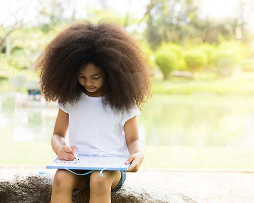 Young black girl writing on a white board outside.