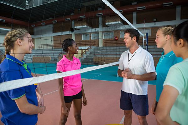 Male volleyball coach talking with a variety of teen girls.