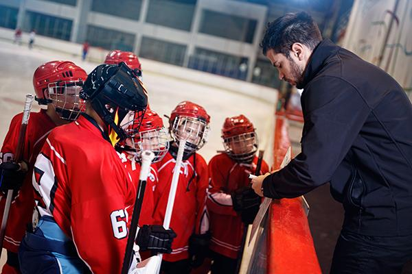 Hockey coach talking to young team members.