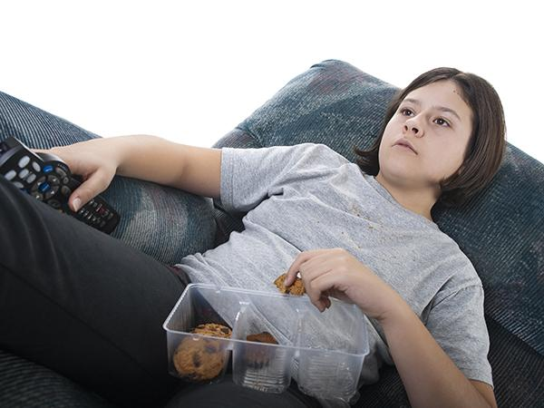Young male child sitting in recliner eating cookies while holding a television remote.