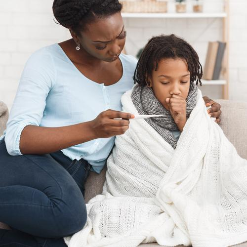 Black mother comforting sick child while looking at thermometer.