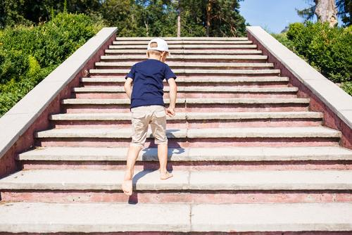 Barefoot young white male child going up stairs outdoors.