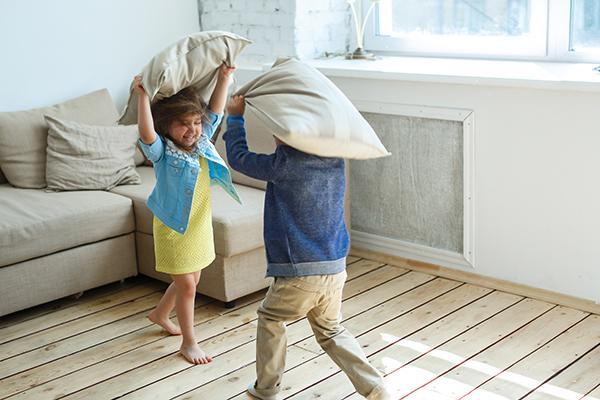 A boy and girl sibling having a fun pillow fight.