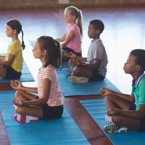 Group of diverse school-age children meditating on yoga mats.