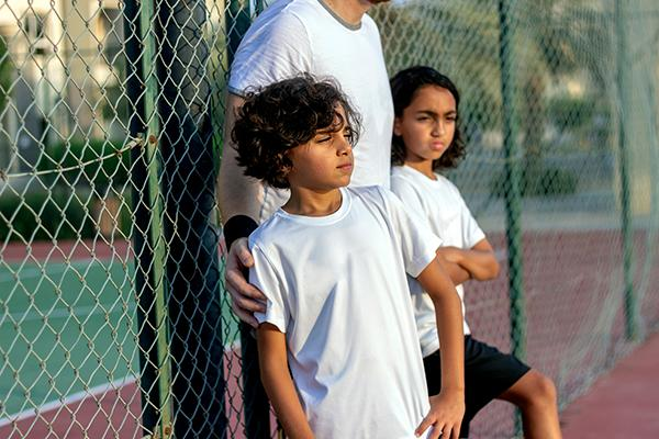 Two upset youth athletes on sidelines of tennis court with coach.