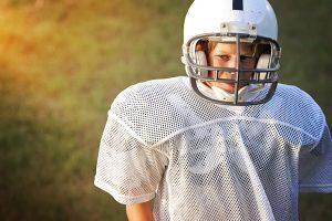 Young white football player standing alone looking upset.