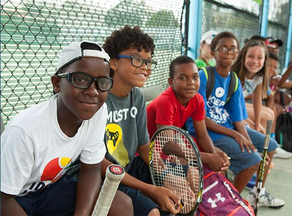 Young diverse tennis athletes looking at camera.