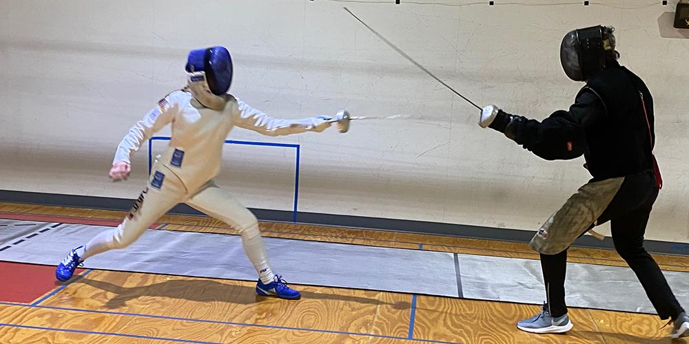 Coach Benoit Bouysset fencing with a young athlete.