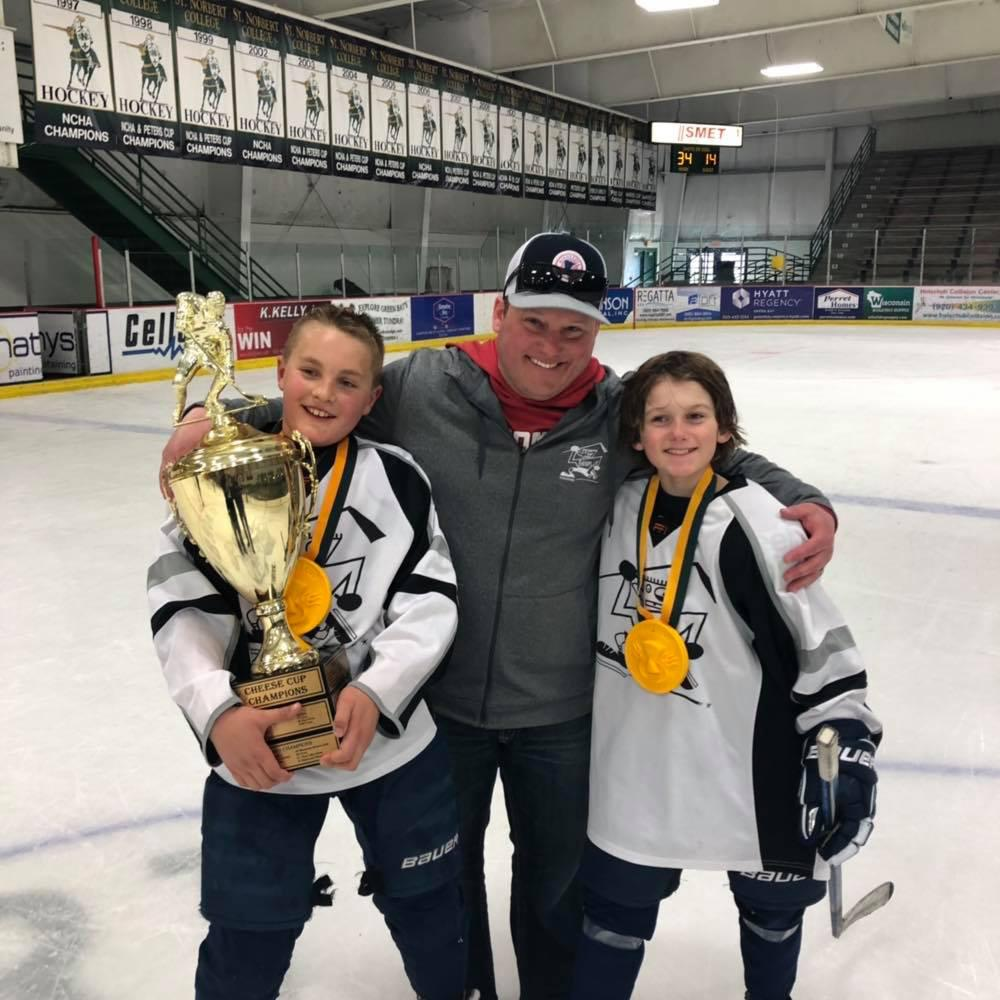 Ice hockey coach Greh Krahn with two young athletes.