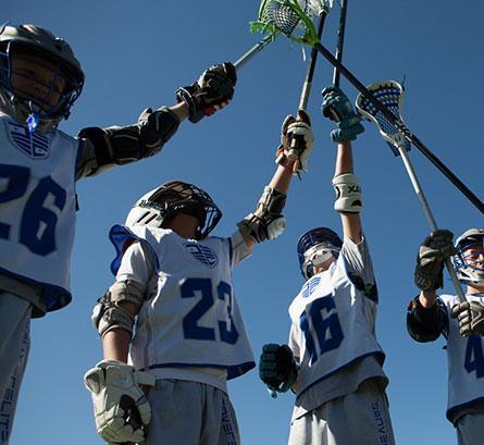 lacrosse players raising sticks