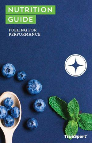 TrueSport Nutrition Guide: Fueling for Performance cover image of blueberries on a wooden spoon.