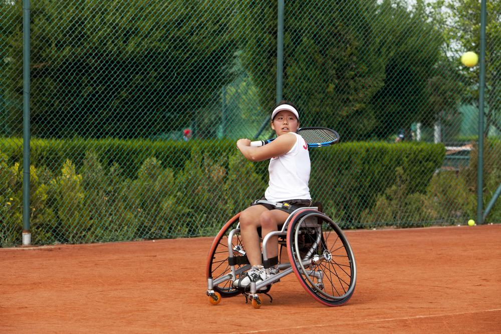Young female wheelchair tennis player during game.