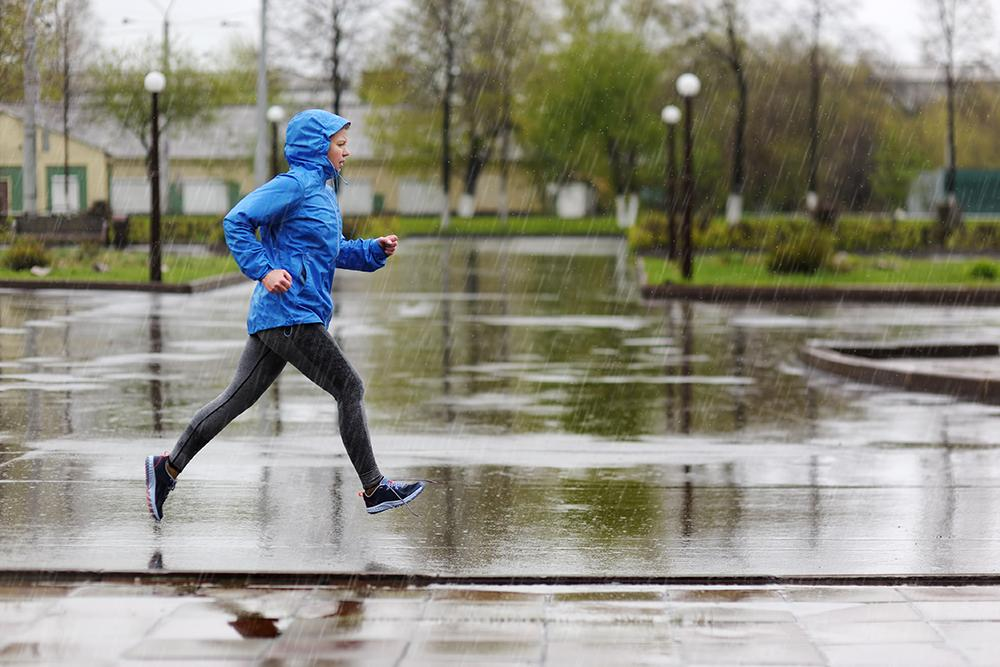 Woman running in rain.