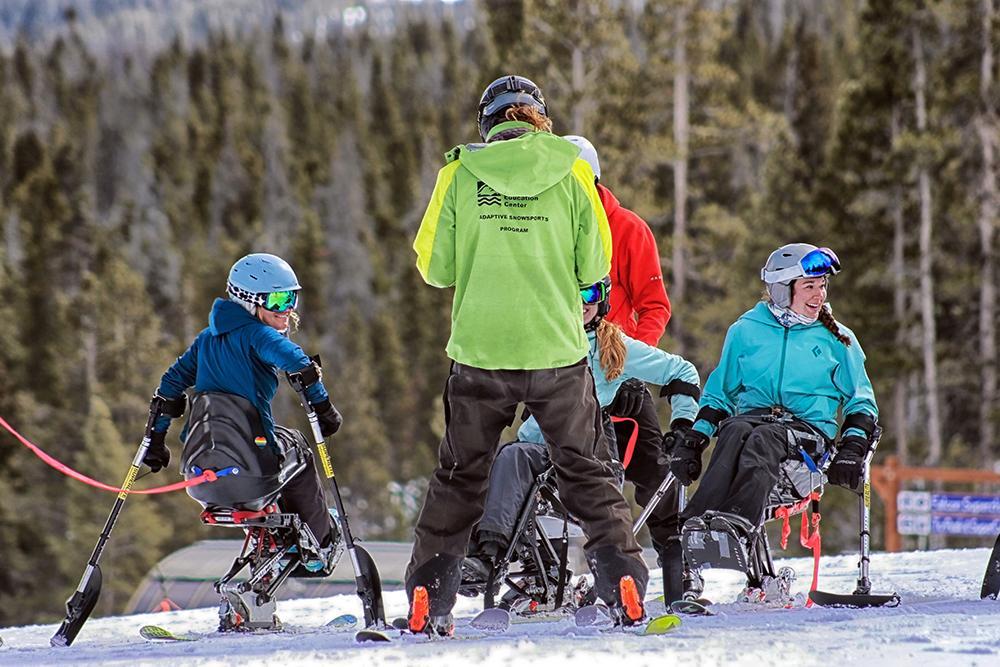 Small group of women adaptive skiing.