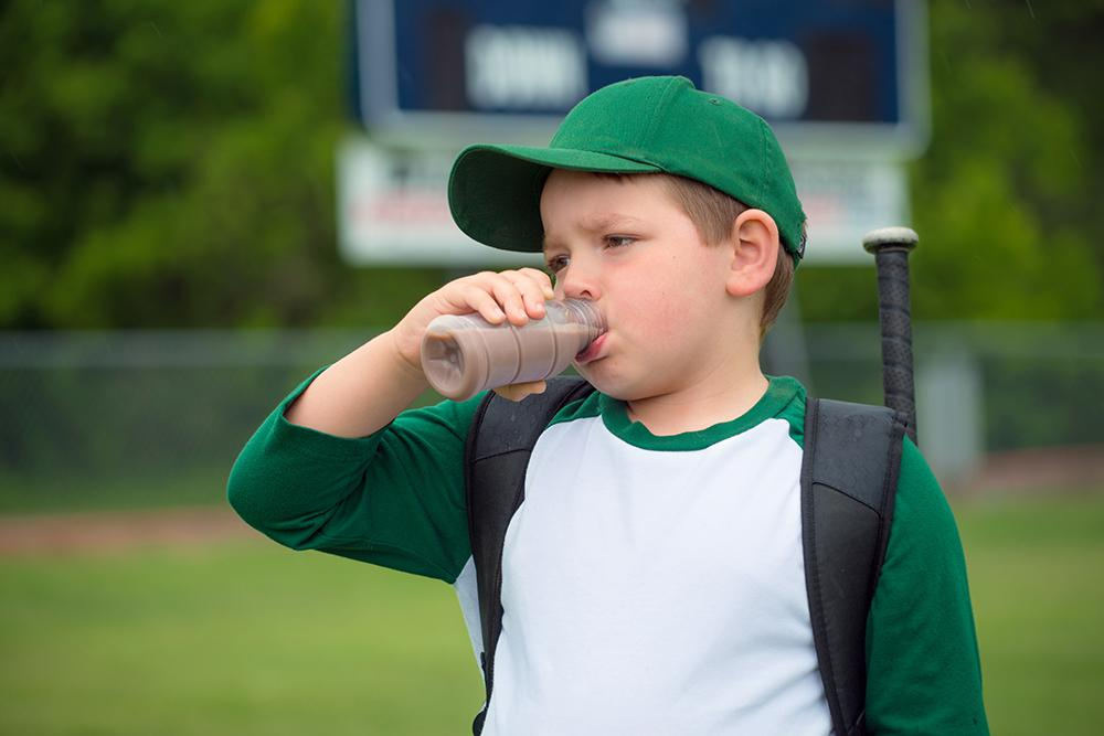 Young white male baseball player drinking chocolate milk.