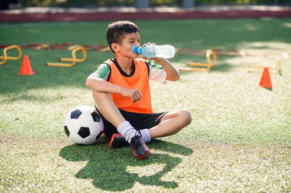 Young male soccer player sitting on the field drinking water.
