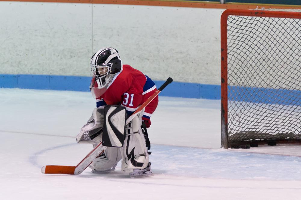 Young kid hockey goalie alone in front of goal on ice.