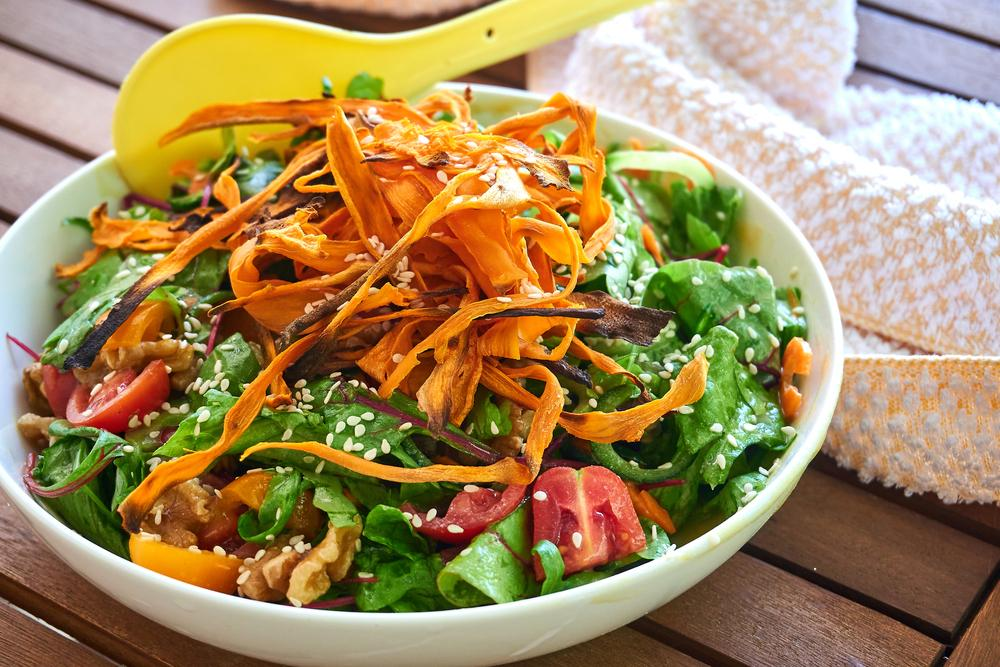 Big bowl of salad with shaved carrots on top.