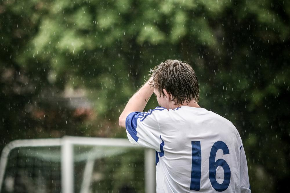 Football player standing alone in the rain.