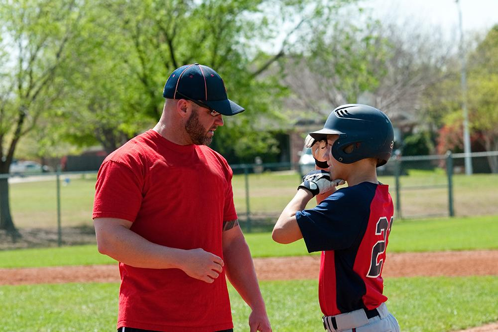Baseball coach talking to young male athlete.