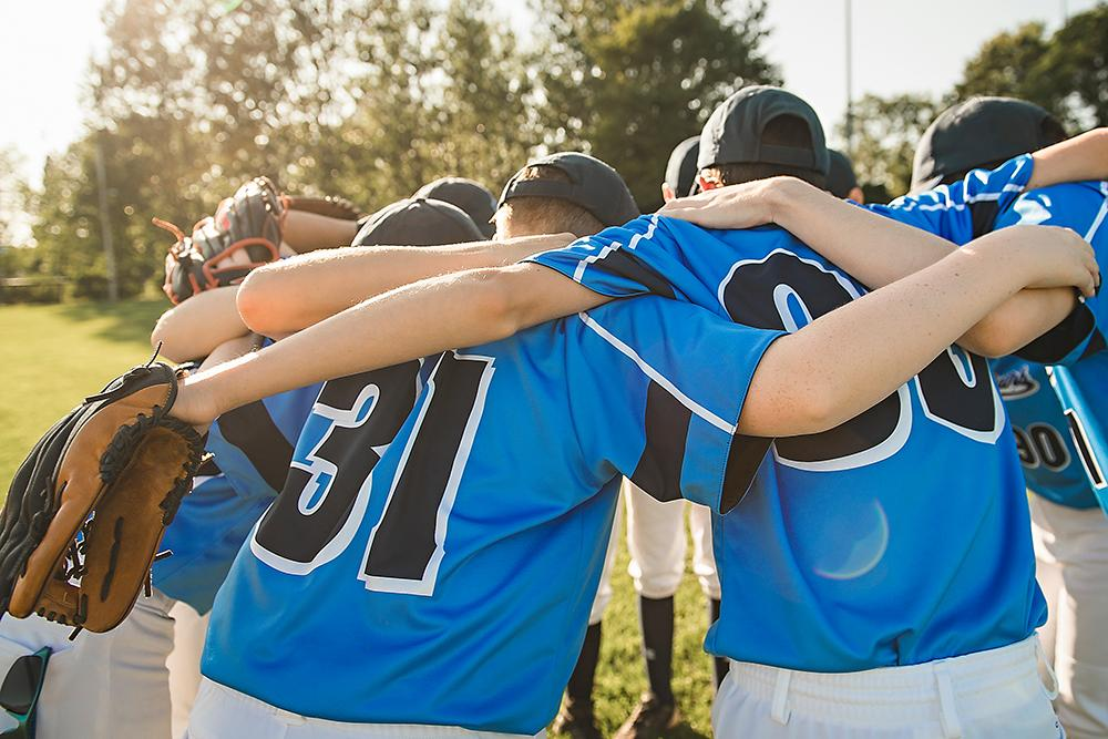 Teen baseball team in a huddle.