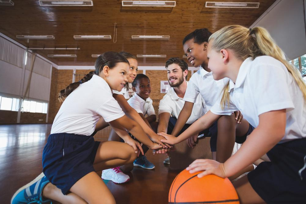 Young girl's basketball team in a huddle with coach.