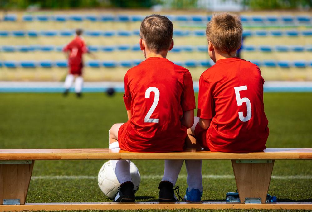 Two young boys on bench during soccer game.