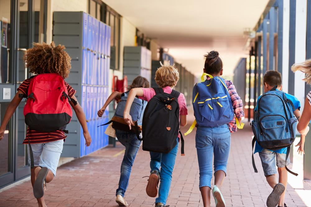 Diverse group of kids running down a school hallway with backpacks on.