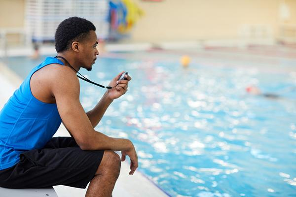 Black male swim coach timing swimmers in indoor pool.