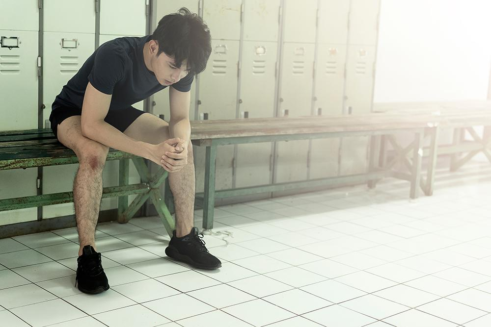 Young asian man sitting alone in locker room.