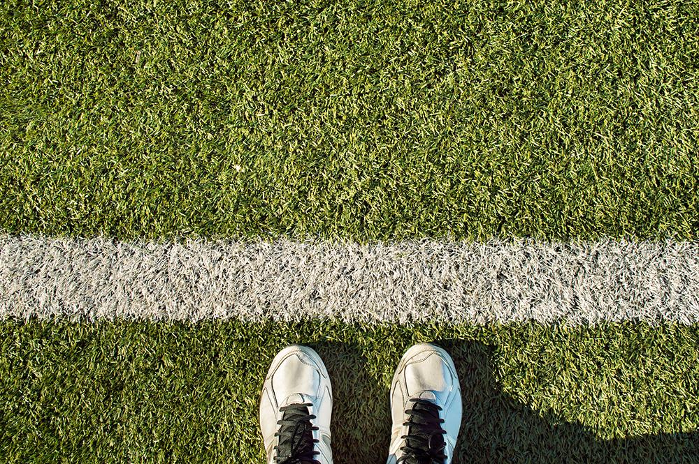 Sneakers toeing a line on a field.