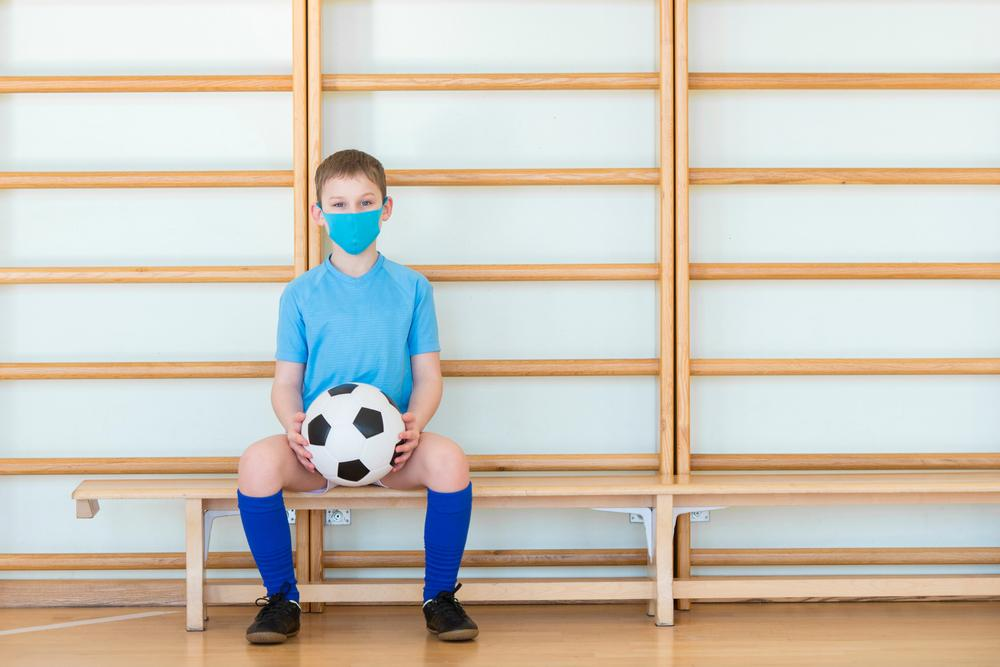 Young boy sitting on indoor bench wearing a mask and holding a soccer ball.