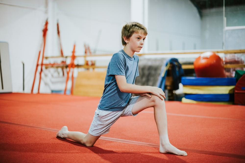 Young boy stretching before gymnastics.