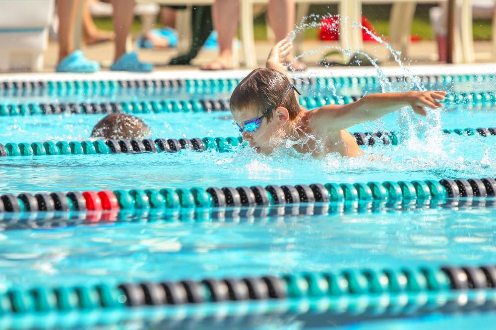 Young boy competing in a swim competition.