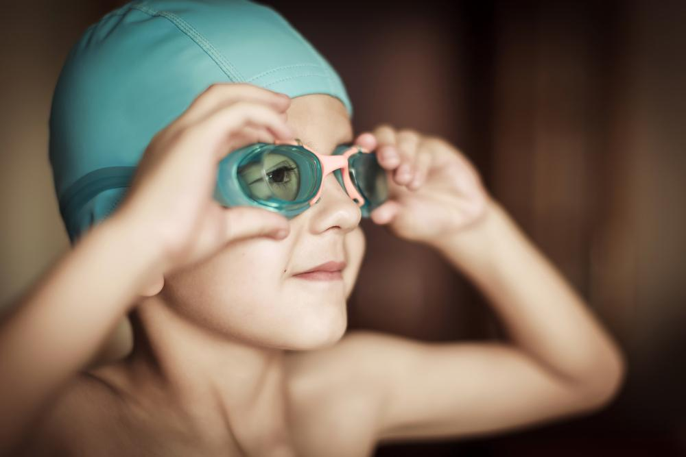 Close up of young boy wearing swim cap and goggles.