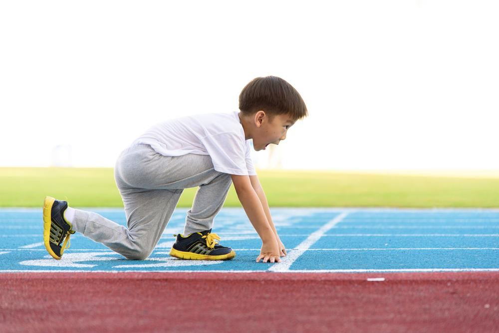 Young asian boy on a track about to run.