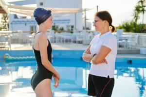 Swimming coach talking to young female athlete.