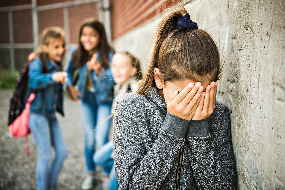 Young girl being bullied by three other girls.