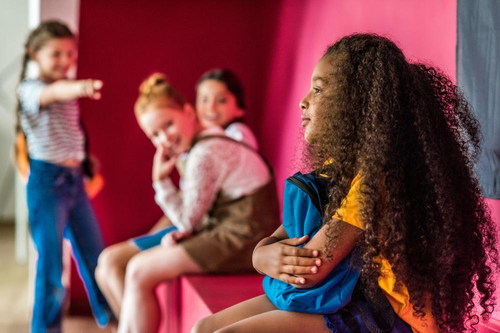 Young girls bullying a young black girl.