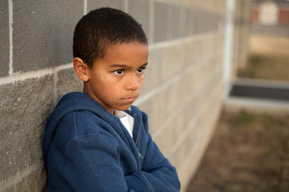 Young black boy leaning on wall looking upset.